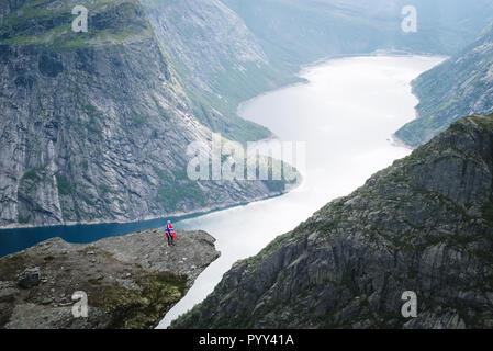 Trolltunga randonnée. - Lac Ringedalsvatnet dans la municipalité de Odda dans Hordaland County, en Norvège. Fille avec pavillon norvégien Banque D'Images