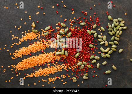Lentilles sèches et de soja avec poivre rouge éparpillés sur fond naturel de l'ardoise Banque D'Images