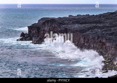 De grosses vagues se briser contre les falaises volcaniques hautes sur Hawaii's Big Island, dans le Parc National du Volcan. Océan Pacifique dans l'arrière-plan.