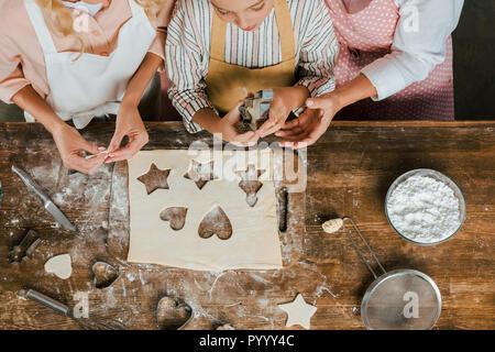 Cropped shot d'enfant avec la mère et grand-mère de préparer les biscuits de Noël à la maison et looking at camera Banque D'Images