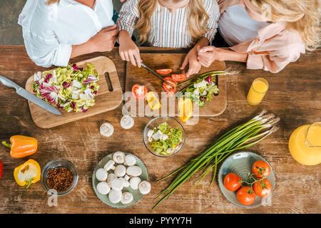 Cropped shot of enfant couper des légumes pour salade avec mère et grand-mère à la maison Banque D'Images