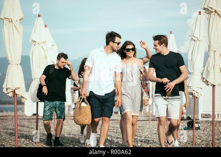 Jours fériés, vacances. groupe d'amis s'amuser sur la plage, marcher, boire de la bière, souriant et serrant Banque D'Images