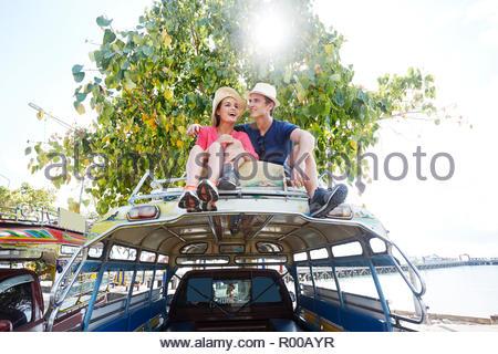 Jeune couple assis sur le toit des autobus d'excursion Banque D'Images