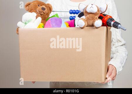 Woman hand holding boîte de dons de vêtements, jouets et livres