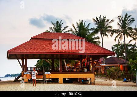 Summer resort à Ko Samui, Thaïlande. Bungalow peu cachés dans les arbres avec de l'eau au coucher du soleil sur la plage Banque D'Images