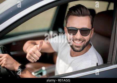 Jeune homme élégant au volant d'une voiture décapotable Banque D'Images