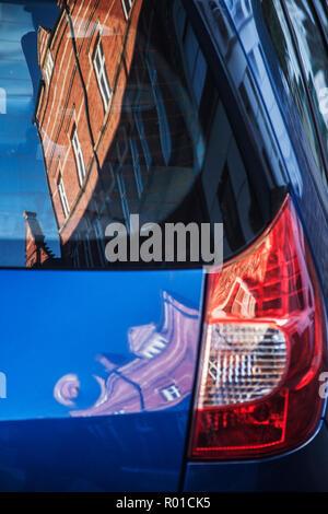 Bâtiment en briques rouges de style victorien réflexion déformée dans l'arrière de la voiture Banque D'Images