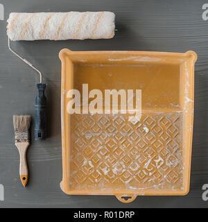 L'objet d'outils de peinture, peinture concept travailleur brosse rouleau blanc et couleur de peinture utilisée dans un plateau en plastique soft focus et sélective pour l'arrière plan. Banque D'Images