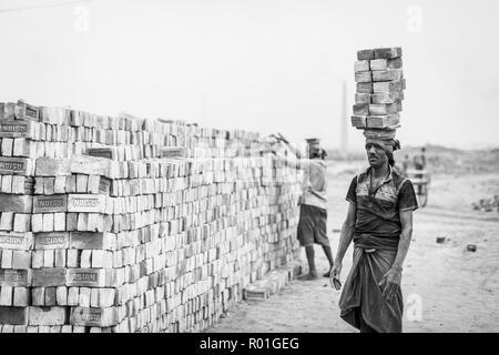 Travailleurs ayant des briques sur la tête dans la briqueterie, monochrome, Dhaka, Bangladesh Banque D'Images
