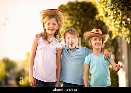 Portrait de trois enfants portant des chapeaux de cow-boy. Banque D'Images
