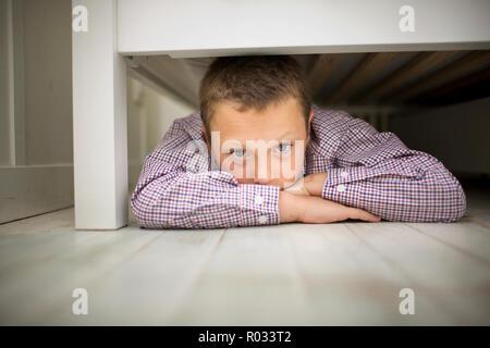 Portrait d'un garçon posé sur son estomac tout en se cachant sous un lit en bois. Banque D'Images