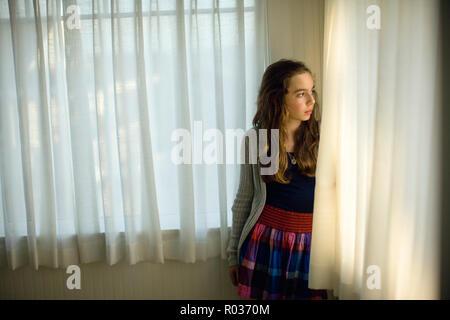 Pensivley fille regarde par la fenêtre de derrière le bord d'un rideau. Banque D'Images
