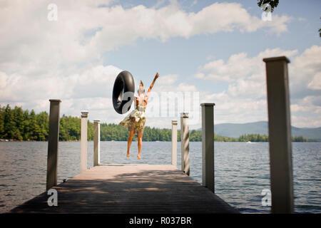 Femme avec tube intérieur, sautant hors d'une jetée dans un lac. Banque D'Images