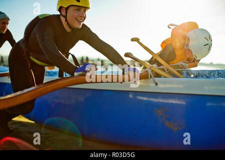 Smiling woman in a helmet et wetsuit pousse sur son canot sur la plage. Banque D'Images