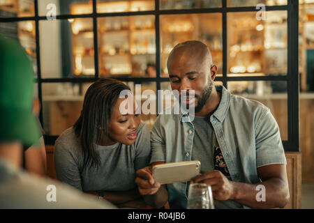 Deux amis assis dans un bar à la recherche de photos de cellulaire