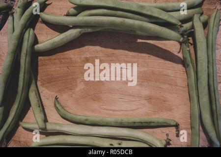 Haricot vert cru entier sur planche à découper en bois, tons vintage Banque D'Images