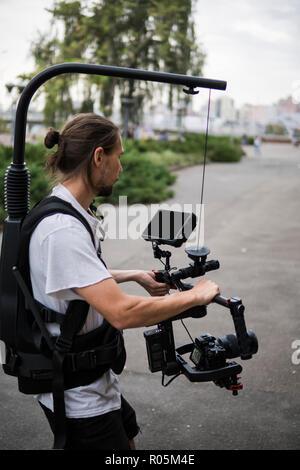 Vidéographe professionnel holding camera sur tourelle 3 axes qui monté sur banc facile. À l'aide d'un vidéographe Steadicam. Matériel Pro aide à faire des vidéos de haute qualité sans agitation. Banque D'Images