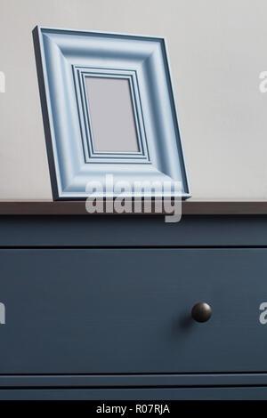 Voir le détail avant verticale de square d'épaisseur sur cadre photo en bois vintage bleu commode avec poignées noires contre le mur dans la lumière naturelle copie