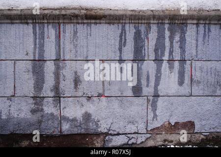 Gris Gris grunge mur de béton avec des taches humides écoulement vertical. Banque D'Images