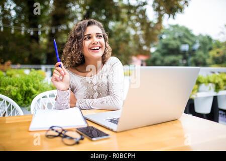 Photo de jeune femme frisée d'Amérique latine excité à l'intérieur à l'aide d'un ordinateur portable à écrire des notes à côté vous avez une idée. Banque D'Images