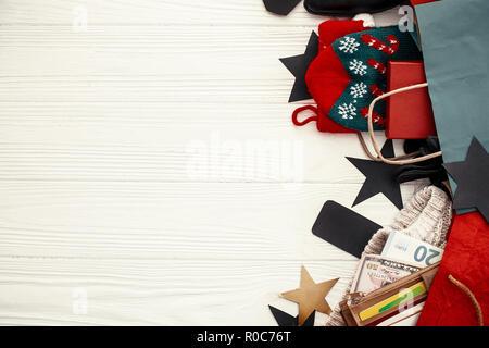 Les achats de Noël et vente de saison. Cartes de crédit et de l'argent dans votre portefeuille, sacs en papier avec des vêtements, des bas, des tags, des boîtes-cadeaux sur bois rustique. Special Banque D'Images