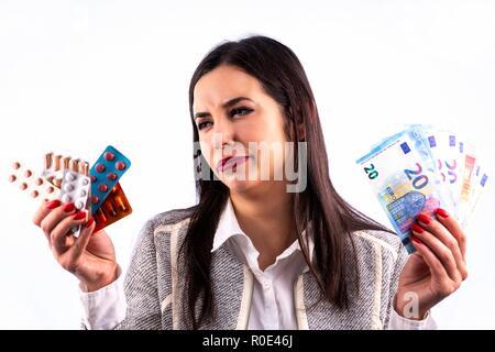Colorés différents comprimés et gélules dans des cloques sur les mains de la belle jeune femme. En regardant les ampoules. Studio shot isolé sur un blanc retour Banque D'Images