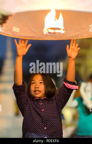 CHIANG MAI, Thaïlande, du 1 er janvier 2015: Une petite fille est l'envoi d'un traditionnel feu de lanterne flottante le ciel et faire un souhait pour la nouvelle année en Banque D'Images