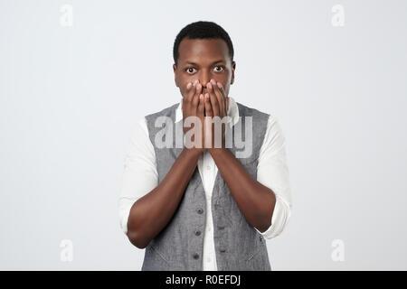 African American jeune homme en chemise blanche et gilet avec main sur sa bouche, stupéfaite et sans voix Banque D'Images
