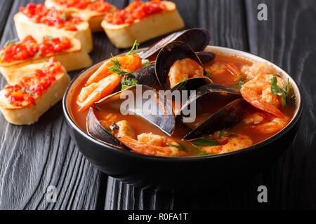 Recette traditionnelle pour la bouillabaisse française avec la soupe aux fruits de mer et poissons close-up dans un bol servi avec des toasts sur la table horizontale. Banque D'Images