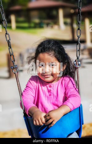 Jeune fille assise latino dans une balançoire portant une chemise rose avec des cheveux en désordre dans un parc extérieur. Banque D'Images