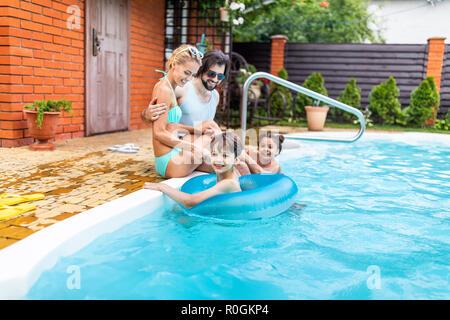 Famille passer du temps près de la piscine de l'arrière-cour d'été sur la campagne Banque D'Images