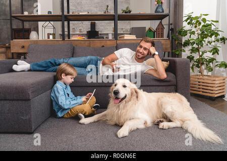 Heureux père regardant la TV sur la table pendant que son fils à l'aide de tablette sur marbre avec golden retriever Banque D'Images
