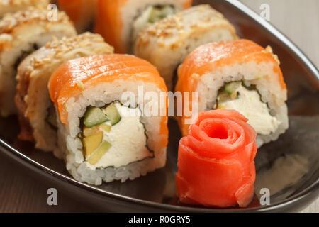 Close up gingembre mariné sous forme de rose rouge et rouleaux de sushi Uramaki - Philadelphie, avec Uramaki Congre sur l'arrière-plan. La cuisine japonaise. S Banque D'Images