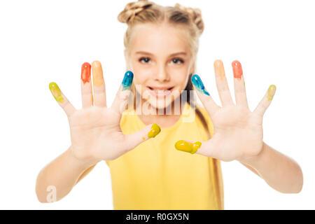 Heureux l'enfant peint en couleurs montrant les mains et smiling at camera isolated on white Banque D'Images