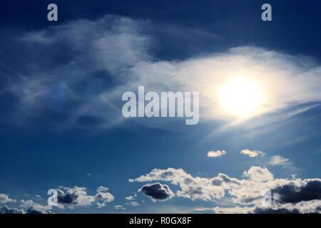 Soleil clair avec l'auréole à travers les nuages cirrus contre le ciel bleu Banque D'Images