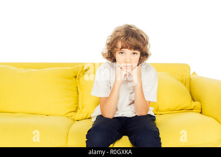 Fâché garçon assis sur le canapé jaune de mains et isolé sur blanc, looking at camera Banque D'Images