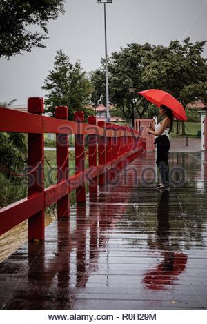 Belle course mixte Asian young woman holding parapluie rouge sur un pont rouge sous la pluie. Reflet de femme et parapluie en flaque. Banque D'Images
