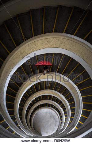 Mixed Race belle jeune femme tenant parapluie rouge debout au bord d'une spirale de 5 étages. stairscase À partir de ci-dessus. Parc public à Singapour Banque D'Images