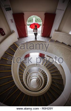 Mixed Race belle jeune femme tenant parapluie rouge debout au bord d'une spirale de 5 étages. stairscase Parc public à Singapour Banque D'Images