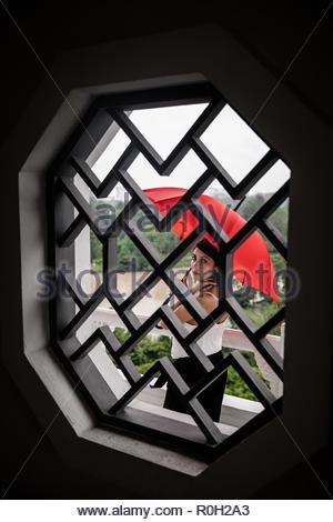 Mixed Race belle jeune femme tenant parapluie rouge à travers une fenêtre à l'appareil photo. Parc public à Singapour Banque D'Images