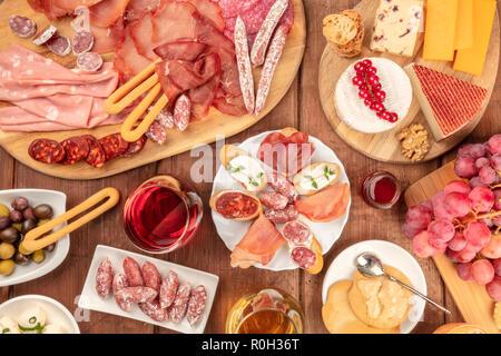 Dégustation de charcuterie. Une photo d'un grand nombre de saucisses et de jambons, charcuteries, et une assiette de fromage, tourné à partir de ci-dessus, sur un fond rustique avec du vin rouge