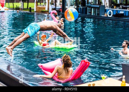Jeune homme sauter dans une piscine pendant que ses amies se reposant sur des matelas gonflable Banque D'Images