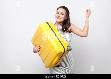 Cheerful young voyageur en robe rayée debout et tenant valise jaune et montrant les muscles avec sourire à pleines dents et prêt pour les vacances. Piscine st