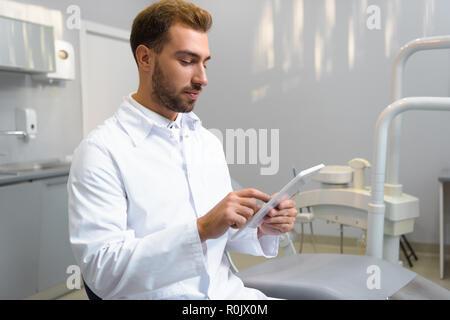Beau jeune dentiste à enduire à l'aide de tablet in office Banque D'Images