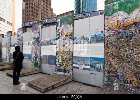Une femme visite un photo gallery organise entre quelques morceaux du mur de Berlin à la Potsdamer Platz, le 15 avril 2017 à Berlin, Allemagne Banque D'Images
