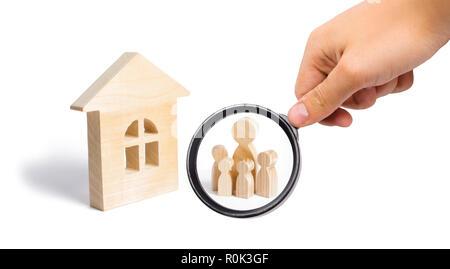Loupe à la recherche à la jeune famille avec enfants est debout près d'une maison en bois. Les prêts pour l'achat d'un logement abordable. concept o