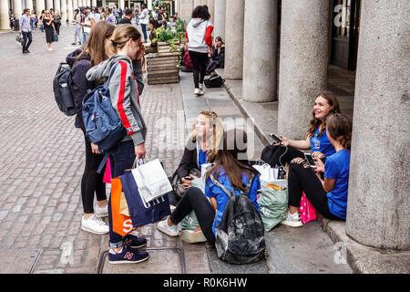 Londres Angleterre Royaume-Uni Grande-bretagne Covent Garden Market market shopping restauration divertissement plaza piazza girl teen amis étudiants assis o Banque D'Images