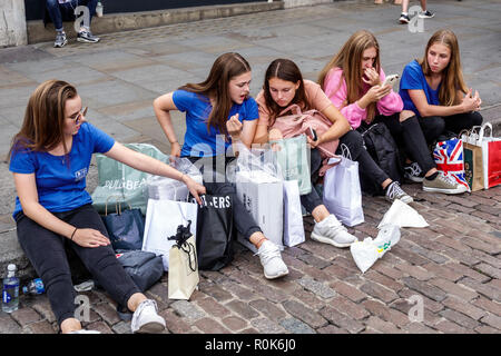 Londres Angleterre Royaume-Uni Grande-bretagne Covent Garden Market shopping restauration divertissement plaza piazza girl teen student friends sitting on curb Banque D'Images