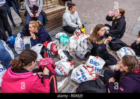 Londres Angleterre Royaume-Uni Grande-bretagne Covent Garden Market shopping restauration divertissement plaza piazza girl teen amis étudiants assis sur cobbl Banque D'Images