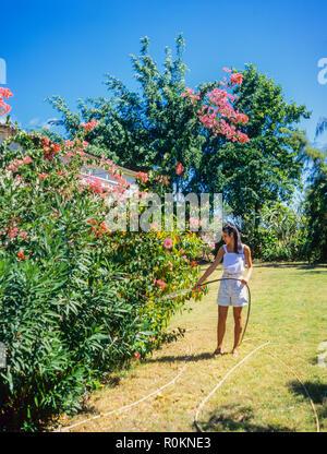 Jeune femme d'arroser les fleurs et plantes, jardin tropical, Guadeloupe, French West Indies, Banque D'Images